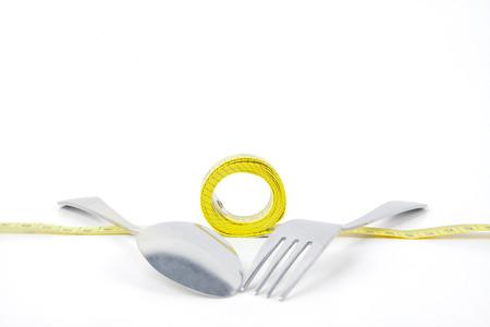 metro medir: Cuadro de la cuchara de acero y un tenedor en una cinta métrica de medición de color amarillo, aislado en fondo blanco Foto de archivo