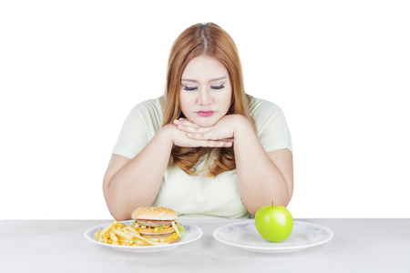 Portrait of overweight woman looks doubtful to choose a fresh apple fruit or hamburger, isolated on white background