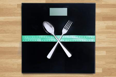 weigher: Close up of measuring tape and crossed cutlery on a weigher machine with wooden background Stock Photo
