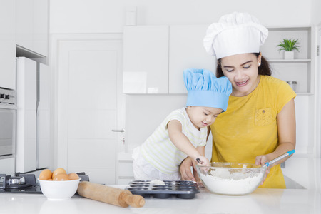 Portrait of beautiful mother teaching her cute child making cookie with flour in the kitchen
