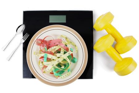 Top view of colourful measuring tape on a plate with scales between cutlery and two dumbbells on white background Stock Photo