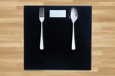 weigh machine: Close up of steel spoon and fork on weight scales on the wooden table