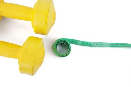 metro de medir: Imagen de dos pesas de color amarillo con un rollo de cinta de medición del medidor, aislado en fondo blanco