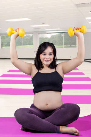 expectant: Picture of a young expectant woman doing workout with two dumbbells at gym while sitting on the mat
