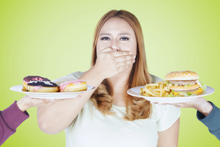 to restrain: Portrait of fat woman rejects high calorie food while closed her mouth with hand