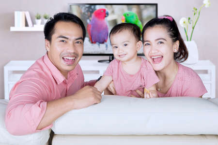 happy smiling: Portrait of happy family sitting on the sofa while smiling at camera in the living room Stock Photo