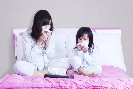 Portrait of sick woman and child wiping their nose using tissue and sitting on the bed Banque d'images