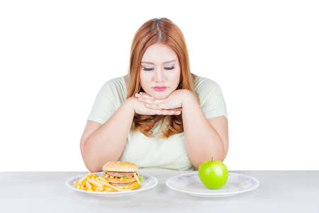 Ritratto di donna in sovrappeso sembra dubbioso di scegliere un frutto mela fresca o hamburger, isolato su sfondo bianco Archivio Fotografico
