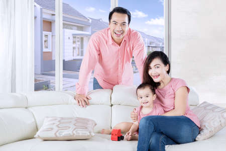 asian family home: Cute daughter sitting on the sofa while playing a toy in the living room with her parents Stock Photo