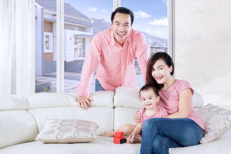 niños sentados: hija linda que se sienta en el sofá mientras se reproduce un juguete en la sala de estar con sus padres Foto de archivo
