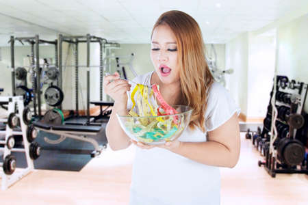 losing control: Portrait of obese woman eats measuring tapes on bowl while standing in fitness center