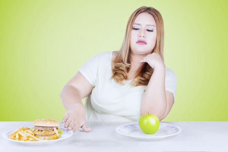 Beautiful blonde woman rejecting a plate of hamburger on the table with a fresh apple fruit on a plate