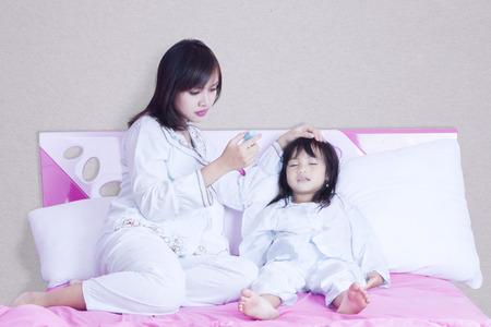 Portret van jonge moeder het controleren van de temperatuur van haar kind tijdens het kijken van de thermometer
