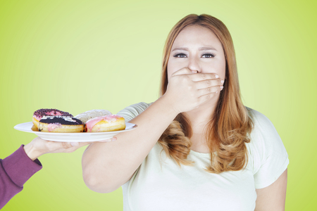 Portrait of young woman closed her mouth while refuses a plate of donuts