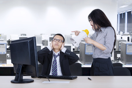 disdain: Image of an angry female employee shouting at her manager through megaphone while working with a computer in the workplace