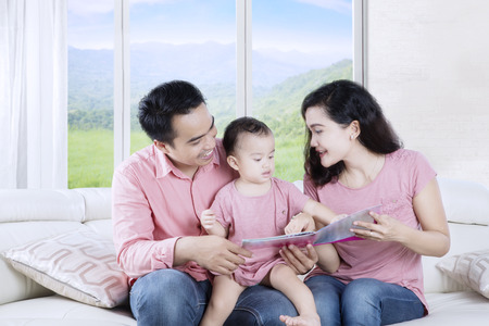 kinship: Image of cheerful Asian parents sitting on the couch while reading a story tale with their daughter at home Stock Photo