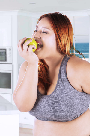 Pretty blonde woman wearing sportswear and eating a fresh apple fruit in the kitchen at home