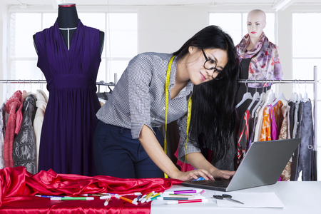 designer: Beautiful female fashion designer working on the table with a laptop computer and clothes hanger on the background Stock Photo