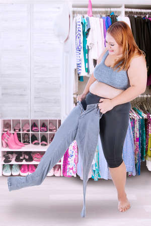 tight body: Full length of blonde woman trying to wear her old jeans at home with wardrobe background