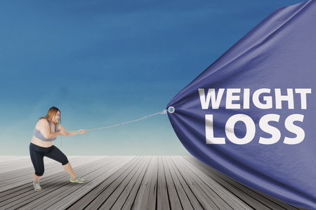 Overweight woman with blonde hair, wearing sportswear and pulling a big flag with text of weight loss