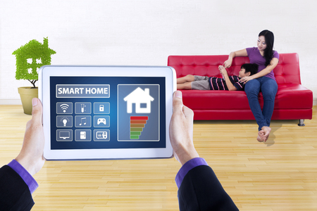 women sitting: Image of controller app of smart house system on the digital tablet screen. Shot with little boy using tablet with his mother on sofa
