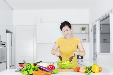 chinese spinach: Pretty Asian woman cooking vegetables in the kitchen while making salad on a bowl Stock Photo