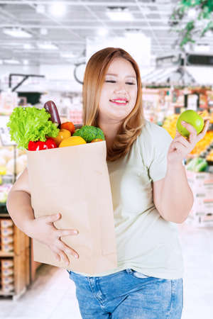 apple paper bag: Image of obese female looking at fresh apple and holding vegetables on paper bag while standing in the market