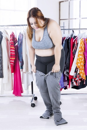 waistline: Picture of overweight woman tries to wear her old jeans with clothes rack in the bedroom