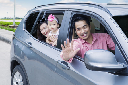 Image of young father waving hands at camera while driving a car with his wife and daughter