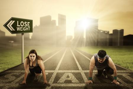 비만인 사람들의 이미지가 시작 라인에서 무릎을 꿇고 경쟁하면서 도로 표지판에서 체중 감량 텍스트로 꿈을 쫓으려고합니다.