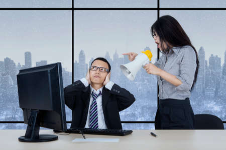 disdain: Young female employee is shouting at her manager through megaphone while working and sitting in the office with autumn background on the window