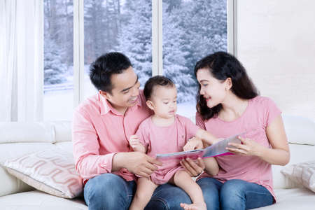 storybook: Picture of young parents reads a storybook to their daughter at home with winter background on the window