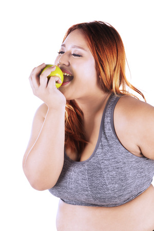 Portrait of beautiful blonde woman with overweight body, eating a green apple fruit while wearing sportswear in the studio Stock Photo