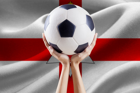 Two arms holding a soccer ball with national flag background of Northern Ireland
