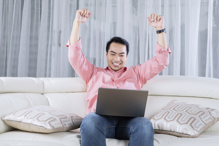 freelancers: Image of cheerful young male using a laptop while raising hands up and sitting on the couch