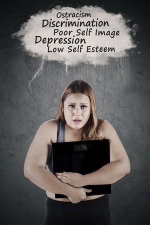 low self esteem: Portrait of a fat woman holding a weighing scale and looks frustrated, thinking her problems