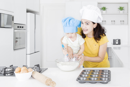 mama e hija: Cute little girl and her mother making cake in the kitchen while wearing cooking hat Foto de archivo