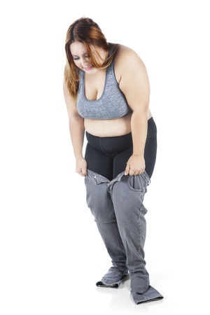 tries: Image of overweight young woman tries to wear her old jeans in the studio