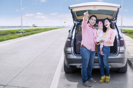 Happy family holding a digital tablet and looking at something while standing behind a car on the street Banque d'images