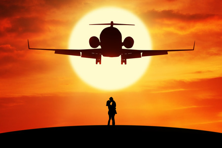 trip over: Silhouette of young couple standing on the hill and kissing under a flying airplane at sunset time