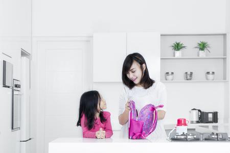 부엌에서 젊은 어머니의 초상화와 그녀의 딸 준비 학교 가방