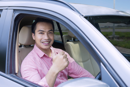 Image of happy young male driving a new car while showing thumb up and looking at the camera Stock Photo