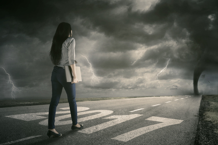 Picture of a female employee walking on the road while carrying a laptop with storm on the sky