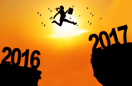 Concept of New Year 2017. Silhouette of a young businesswoman jumping between numbers 2016 and 2017 above cliff