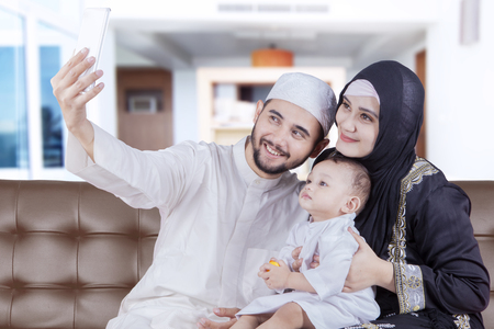 Arabian family taking selfie photo by using smartphone while sitting on the sofa Stock Photo