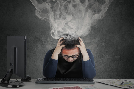 dizzy: Picture of young woman feeling dizzy with financial chart on desk while smoke coming out of her head Stock Photo