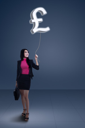 libra esterlina: Joven empresaria sosteniendo el símbolo de moneda de la libra esterlina