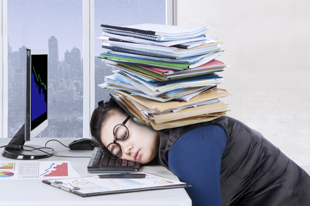 Female entrepreneur feels tired with pile of documents over head while sleeps on the desk, winter background on the window