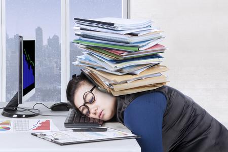 Vrouwelijke ondernemer voelt zich moe met een stapel documenten over het hoofd tijdens het slapen op het bureau, winter achtergrond op het raam