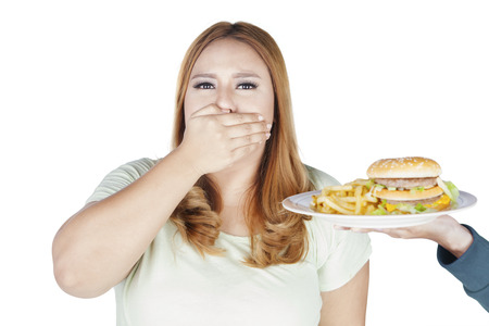 Portrait of fat woman closed her mouth while refusing hamburger and french fries, isolated on white background